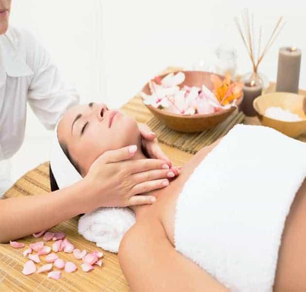 Female receiving light aromatherapy massage to neck area