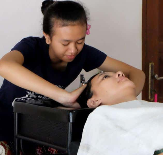 Bali BISA student practicing traditional creambath head massage during shampoo
