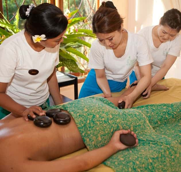 Bali BISA explaining to students about warm stone massage on the legs