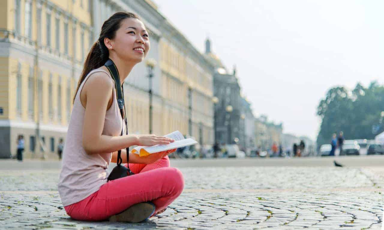A Chinese Girl sit down with book and camera