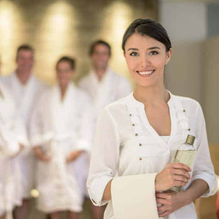 confident-women-smile-with-spa-client-behind