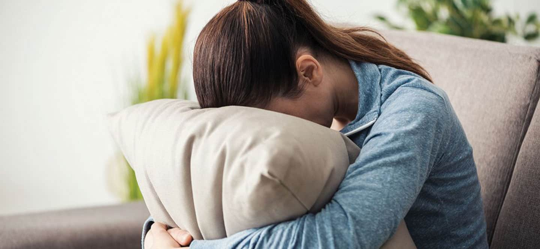women feeling stress hide her face behind pillow