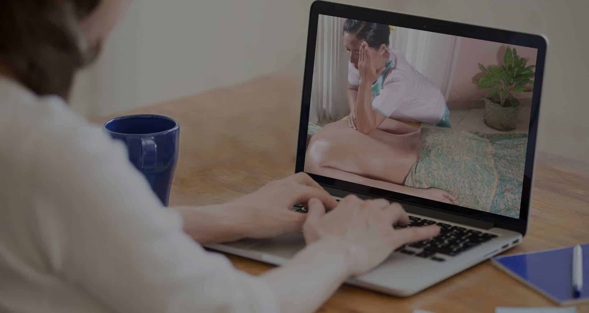 A woman play massage training video on her laptop